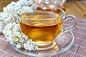 stock photo of teapot  - Yarrow tea in a glass cup and teapot - JPG