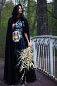 foto of cloak  - girl in a black cloak with a lantern on the bridge - JPG
