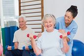 stock photo of senior class  - Portrait of happy senior woman lifting dumbbells while sitting with man and trainer in gym - JPG