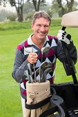 stock photo of buggy  - Happy golfer beside his golf buggy on a sunny day at the golf course - JPG