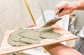 foto of mason  - construction mason man hands on tiles work with cement mortar - JPG
