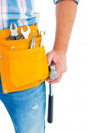 stock photo of handyman  - Midsection of handyman wearing tool belt while holding hammer on white background - JPG
