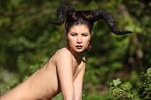 stock photo of hells angels  - The beautiful young girl with horns like devil or angel outdoor - JPG
