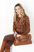 image of woman boots  - portrait of sitting woman wearing brown clothes and boots with a handbag - JPG