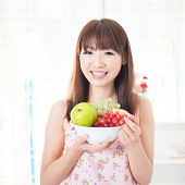 stock photo of apron  - Happy Asian housewife with apron holding fresh fruits - JPG