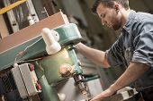 picture of sawing  - Experienced carpenter using sawing machine in factory - JPG