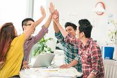 stock photo of enthusiastic  - Young enthusiastic business team giving high five - JPG