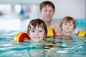 image of floaties  - Young father teaching his two little sons to swim in an indoor swimming pool - JPG