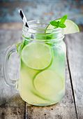 stock photo of mason  - homemade lemonade with lime mint in a mason jar on a wooden rustic table - JPG