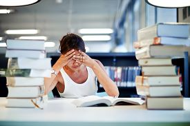picture of piles  - Frustrated female student sitting at the desk with a huge pile of study book in university library - JPG