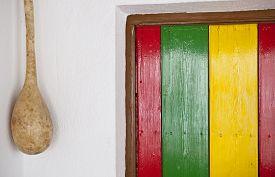 stock photo of reggae  - Reggae bright colors over wooden door and hanging decorative pumpkin - JPG