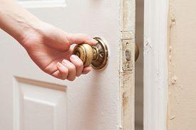 stock photo of door-handle  - Human hand holding door handle and opening the door close up - JPG