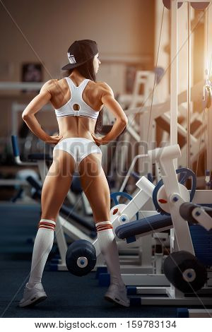 poster of Crossfit woman standing with her back in the gym. Fitness woman, trained body, fitness model. Bodybuilder woman in the gym. Perfect fitness woman sexy buttocks in lingerie. Fitness and bodybuilding