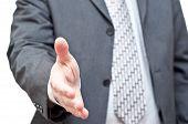 Businessman In Dark Suit Extending Hand To Shake