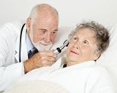 Doctor using an otoscope to examine a hospital patient's ear canal.