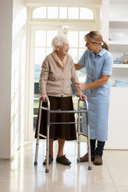 picture of zimmer frame  - Carer Helping Elderly Senior Woman Using Walking Frame - JPG