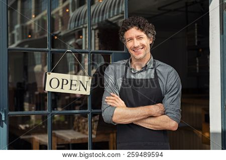 poster of Portrait of small business owner smiling and standing with crossed arms outside the cafe. Portrait o
