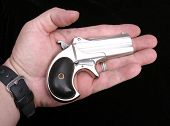 Circa 1889, Model 95, Type II Model 3 Double Derringer, in the palm of a mans hand showing the small