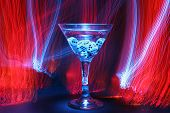 bulb exposure aka Time Laps of a Martini glass with gambling dice in liquid with red orange yellow a