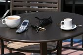 coffee and espresso with a cell phone, car keys, sun glasses outside