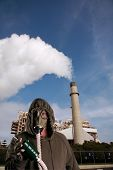 a man in a Gas Mask tries to smoke a cigarette infront of an industrial smoke stack representing Glo