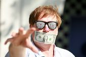 a man wears Hypnotic glasses with a dollar bill taped over his mouth in protest against inflation and the rising cost of goods and services