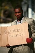 a thursty african american business man stands on a city street with a cardboard sign that reads
