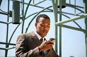an african american business man talks on his cell phone outside of his office building