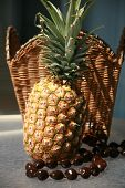image of kukui nut  - a fresh picked pineapple with a Kukui Nut Lei against a wicker basket - JPG