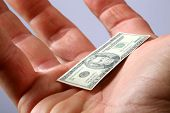 a hand holds miniature money representing the world financial crisis