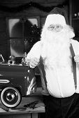 Santa Claus smokes his pipe as he takes a break from building toys for Christmas Presents around the world, in black and white for a Retro look