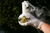 a Scientist holds a 500ml beaker filled with CO2 representing carbon dioxide emmissions and the caus