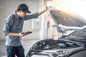 Asian Auto Mechanic Holding Digital Tablet Checking Car Engine Under The Hood In Auto Service Garage poster