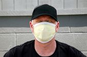 a man wears a yellow medical paper mask as he looks around to stay safe from any air born illness