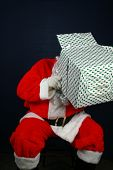 Santa Claus shows his sence of humor by looking inside and wearing a christmas present box on top of