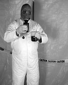 A Nuclear Scientist or Chemical Engineer wears a white Hazmat Suit, Gas Mask, and Gloves as he mixes