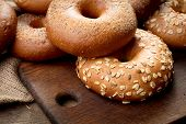 Heap Of Fresh Baked Bagels On Wooden Background poster