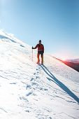 A Man Climbs To The Top Of The Mountain. Mountaineer In Snow Shoes Carry A Backpack. Journey In The  poster