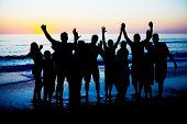 stock photo of beach party  - Silhouettes of young happy people enjoing sunset at the Florida beach - JPG