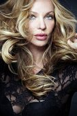 Slim attractive blond woman with long curly hair.