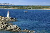 Farol em rochas da Sardenha e um Iate vela no mar