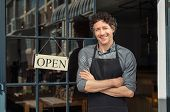 Portrait of small business owner smiling and standing with crossed arms outside the cafe. Portrait o poster