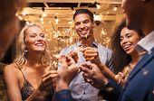 Group of multiethnic friends having fun with sparkling sticks during night party. Group of elegant w poster