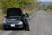 Businesswoman Sat On Her Broken Down Automobile At The Side Of The Road Calling For Help