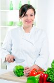 Woman Chef Slicing A Green Pepper Before Cooking A Recipe