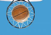 Basketball in the net against clear blue sky - concept of a successful endeavor