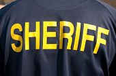Closeup image of a back of a sheriff's deputy, with text sheriff in yellow letters
