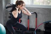 Asian Sport Woman In Sportswear Exercise Squat With With Training Weight Bag In Fitness Gym . Young  poster