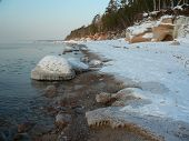 Winter coastline and lovely icicle on stones