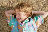 The little boy laying on a dry grass